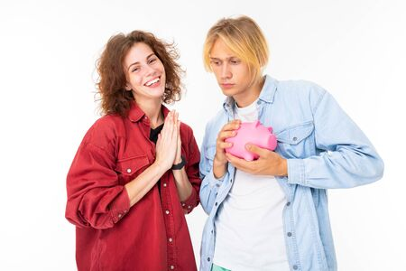 couple in love holds a pink pig moneybox and hopes for money isolated on whitet background. Banco de Imagens