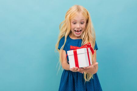 Portrait of little caucasian girl in blue dress with long blonde hair holds white box with a gift and smiles isolated on blue background.