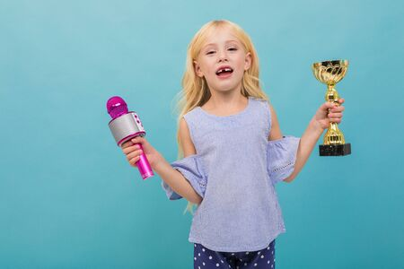 Portrait of little caucasian girl in blue t-shirt with long blonde hair holds a gold cup and microphone isolated on blue background.