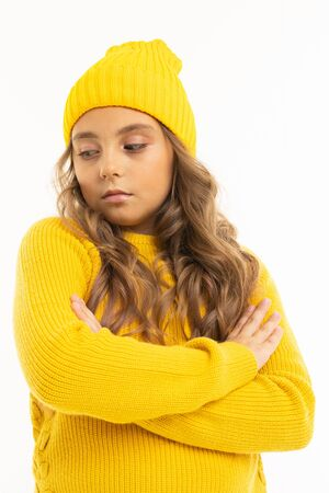 Happy caucasian girl in yellow hat and hoody folded her hands on chest isolated on white background.