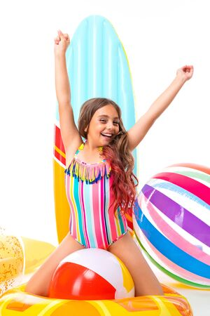 Teenager caucasian girl in red sunglasses, swimsuit, white cap with rubber mattresses isolated on white background Banco de Imagens