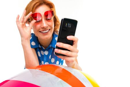 girl leans on an inflatable swimming ball and reads messages on the phone on a white background. Banco de Imagens