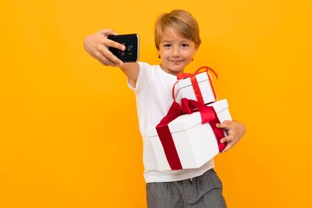 holiday concept. attractive boy with a gift box with a red ribbon takes a selfie on the phone on a bright yellow background.