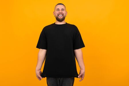 Young tall man with short black hair in black t-shirt smiles isolated on orange background.