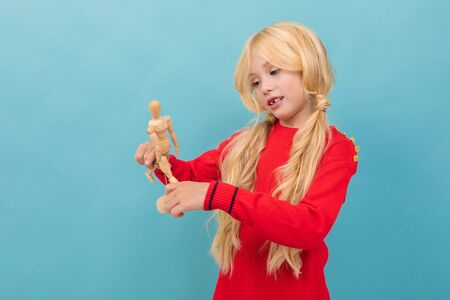A little beautiful girl with long blonde hair braided in tails holds a wooden doll isolated on blue background Banco de Imagens