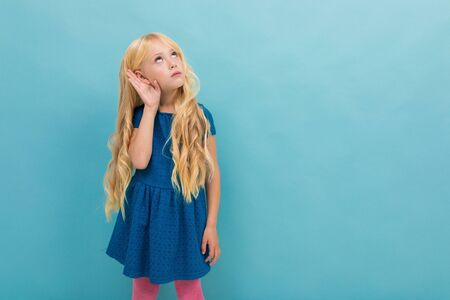 Portrait of little caucasian girl in blue dress with long blonde hair try to hear isolated on blue background.