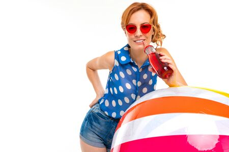 girl in shorts and a t-shirt drinks a cocktail and leans on an inflatable ball on a white background.