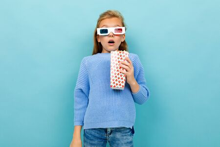 A girl with makeup and long brown hair, 3d glasses looks film or cartoon with popcorn, isolated on blue background