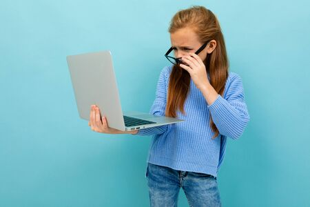 Charming caucasian teenager works or studies with laptop isolated on blue background Banco de Imagens