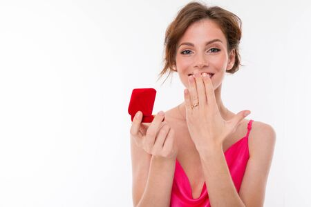 charming girl holds a box with a wedding ring on a white background. Banco de Imagens