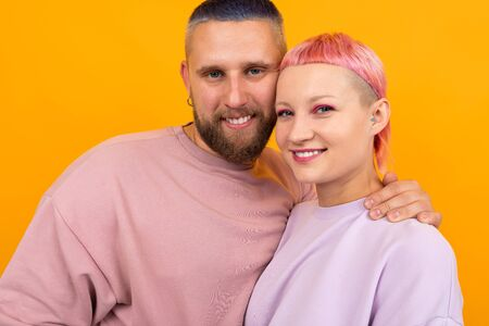valentines day concept. portrait of a happy couple of husband and wife with colored hair and piercings dressed in pink clothes stand in an embrace on a yellow background.
