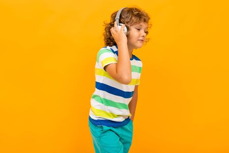 Little boy with curly hair in colourful t-shirt and shorts listen to music with big earphones isolated on yellow background.