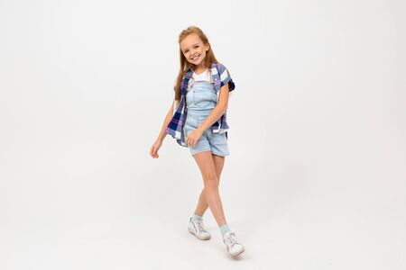 Caucasian teenager girl in stylish clothes dances and enjoy of her life, isolated on white background