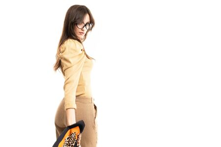 stylish girl in a brown blouse and trousers and glasses with a scarf in her hand on a white background with copy space.