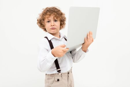 Beautiful boy with curly hair in white shirt, brown hat, glasses with black suspenders holds a laptop isolated on white background.