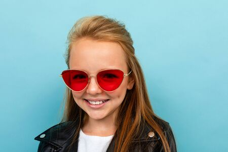 Pretty caucasian teenager girl with brown hair in black jacket holds red sunglasses isolated on blue background. Banco de Imagens
