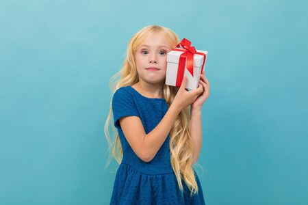 cute blond girl in a dress with a gift in her hands on a light blue background with copy space. 版權商用圖片