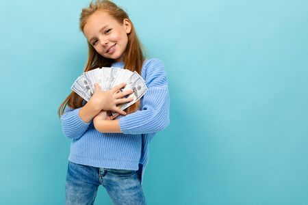 Beautiful teenager girl with long brow hair in blue hoody holds a lot of money isolated on blue background