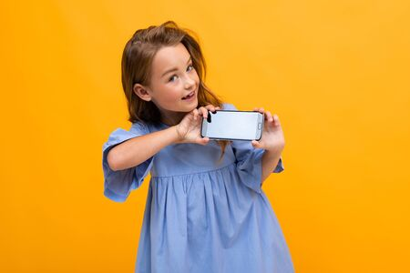cute smiling young girl in a blue dress shows the phone in horizontal position with a mockup on a yellow background with copy space.