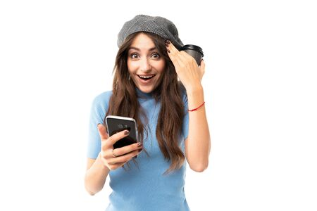 European joyful girl in a beret holds a cup of coffee and reads messages on the phone on a white background.
