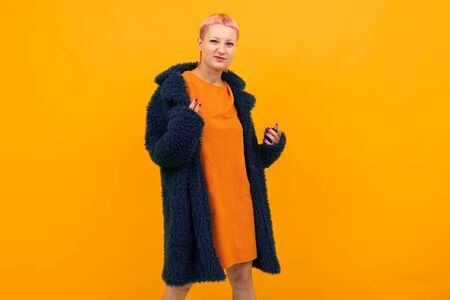 Extraordinary beautiful woman with short pink hair in dark coat smiles isolated on orange background.