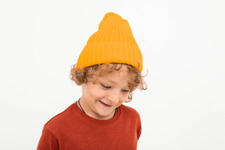 Portrait of charming boy with curly hair, yellow hat smiles isolated on white background.