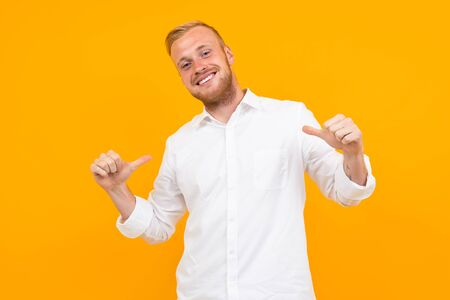 portrait of a blond young man in a white shirt shows himself with a layout on a yellow background.