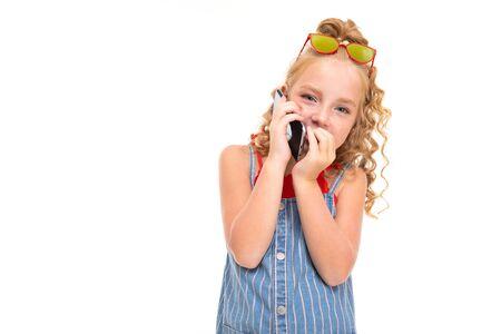 Jolie fille aux cheveux bouclés juste appeler le téléphone et sourires, portrait isolé sur fond blanc