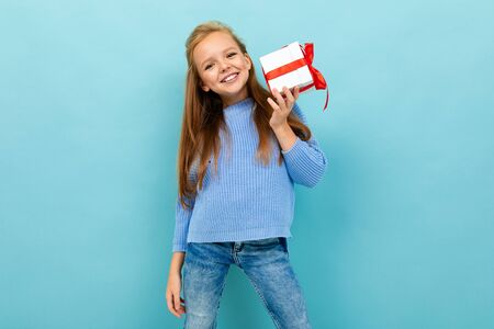 attractive girl stands by the wall with a gift with a red ribbon. Banco de Imagens