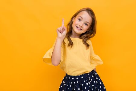 valentines day concept. attractive charming girl child in a T-shirt and skirt shows up to the wall on a yellow background with copy space.