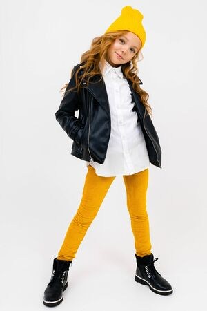 smiling stylish caucasian charming schoolgirl in a white shirt, leather black jacket, with a yellow cap on her head posing on a white background. Banco de Imagens