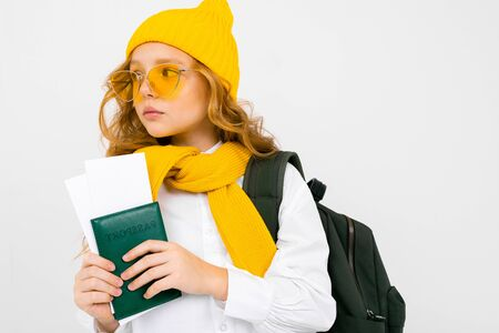 attractive teenager girl with a backpack, scarf, hat and passport with tickets on a white studio background.