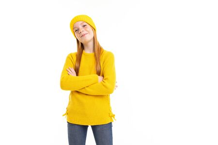 Happy teenager girl with red hair, yellow hoody and trousers thinks about something good isolated on white background. Banco de Imagens