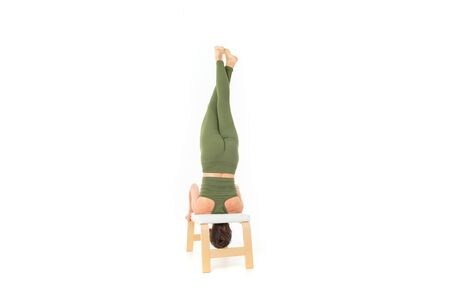 Caucasian gymnast with athletic body stands on her head, does warm-up and stretch muscles.