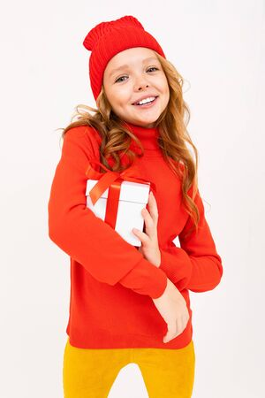 Little caucasian girl in red hoody and hat holds a white box with gift and has a lot of emotions isolated on white background. Banco de Imagens
