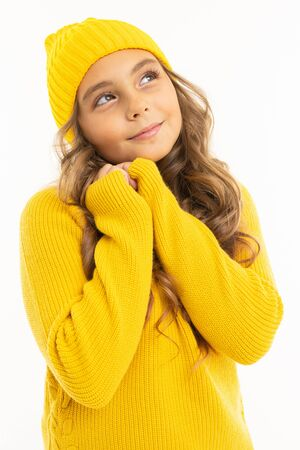 portrait of a cute teenager girl in cozy yellow clothes on a white background.