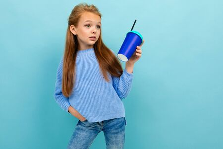 Caucasian teenager drinks coffee with blue cup isolated on blue background Banco de Imagens