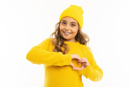 Beautiful caucasian girl with in yellow hoody and hat shows a heart from her hands and smiles, portrait isolated on white background