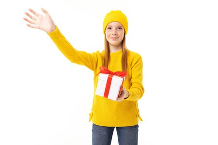 Little caucasian girl holds a white box with gift and has a lot of emotions isolated on white background.