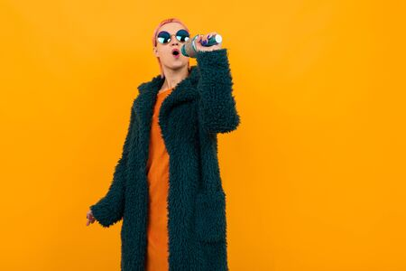 Happy caucasian woman with short pink hair in dark coat and sunglasses sings into a microphone isolated on orange background