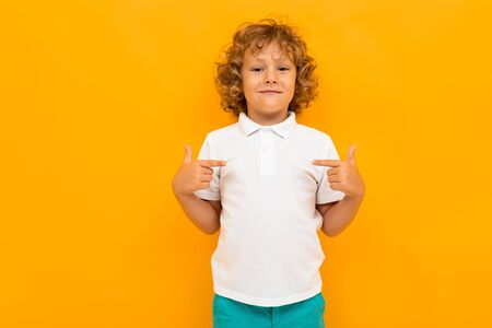 Little boy with curly hair in colourful t-shirt and shorts shows thumbs for himself isolated on yellow background.