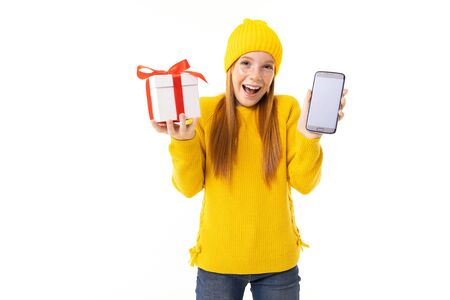 Beautiful caucasian girl in yellow hoody and hat holds a white box with gift in one hand and a smartphone in other hand, smiles and choises between it isolated on white background Banco de Imagens