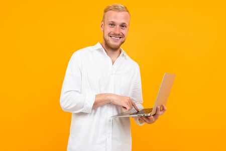 blond attractive businessman is typing on laptop on yellow background. Banco de Imagens