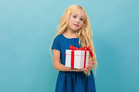 Little caucasian girl holds a white box with gift and has a lot of emotions isolated on blue background