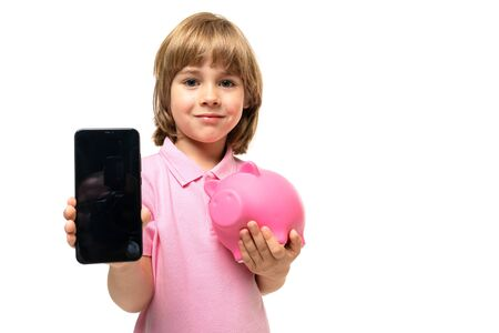 young aattractive boy with a phone with a pink piggy bank mockup on a white background with copy space. Banco de Imagens
