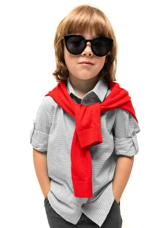 portrait of a boy in a short-sleeved shirt and a knitted sweater with glasses on a white background. Banco de Imagens