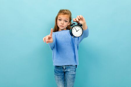 Teenager caucasian girl in blue hoody holds an alarm clock and smiles isolated on blue background
