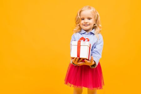 holiday concept. little girl with a gift on a bright yellow background.