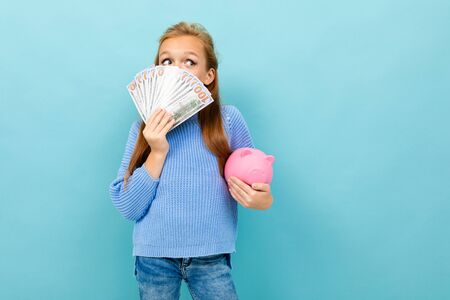 Portrait of little caucasian girl with long brow hair in blue hoody holds pink pig moneybox with a lot of money isolated on blue background