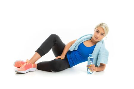 The young sporty girl with a fair hair relax after training isolated on white background. Banco de Imagens